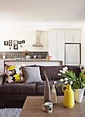 Sofa und Coffee-Table mit Vasensammlung; offene Küche im Hintergrund