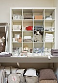 Home accessories in sales room - linen textiles, cushions and crockery stacked on shelves and on floor