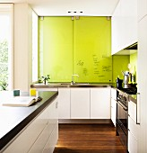 Modern white designer kitchen with writing on lime green sliding cupboard doors above sink