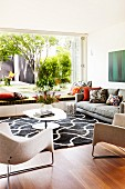 Stylish living room with designer furniture, graphic black and white rug and open terrace window with view into summer garden