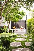 Two orange Butterfly chairs on sunny terrace in garden