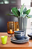 Grey crockery, black and white designer vase, lemon-yellow beaker and glass candle lanterns arranged on table