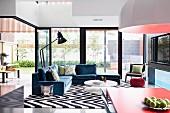 Open terrace doors, black and white zig-zag rug and comfortable grey-blue sofa set in retro, open-plan interior
