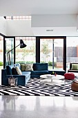 Glass walls, glossy stone floor and striking black and white, retro zig-zag rug in comfortable open-plan living area