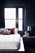Masculine bedroom with dark blue wallpaper and curtains, white bedlinen and Union flag cushion