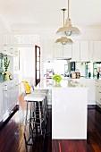 weiße Einbauküche im Landhausstil mit Küchentheke, Barhockern und glänzendem Dielenboden