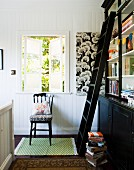 Dark brown bookcase with library ladder in front of open lattice window and wooden, country-house-style chair