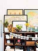 Framed pictures stood on top of antique wooden shelving unit holding various crockery decorated with garland of letters
