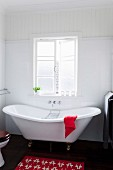 Red bathmat on dark wooden floor beside vintage-style white bathtub below lattice window