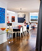 Collection of artworks and children in open-plan family room in contemporary interior decorated in 60s retro style