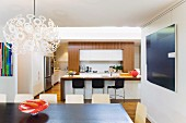 Designer Dandelion pendant lamp, colourful 60s glass bowl and dark dining table in front of breakfast bar in open-plan kitchen