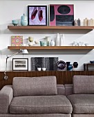 Collection of artworks, ceramic vases and bowls on sideboard behind comfortable designer sofa