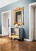 Opulent, Baroque mirror combined with mirrored, Art Deco cabinet in hallway of stylish, Viennese period apartment