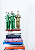 Small, green ceramic sculpture - Mao Zedong flanked by two party members on stack of books