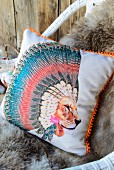 Scatter cushion with motif of lion wearing Native American headdress on cosy sheepskin blanket on wicker chair