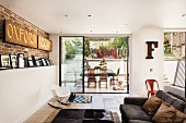 English designer apartment with gallery of photos leaning on wall and exposed brickwork in living area with view of terrace