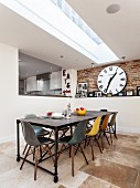 Long dining table, designer chairs of various colours, strip skylight, stone flagged floor and large wall clock on exposed brickwork