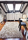 Eclectic postmodern style - white, Rococo-style chests of drawers, long-pile rug and skylight with wide frame