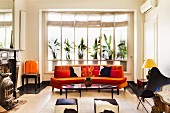 Retro-style seating area with curved orange sofa, cowhide stools, Butterfly Chair and antique fireplace to one side