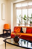 Retro, 70s-style seating area with curved sofa, glass table and table lamp with glass lampshade