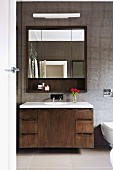 Washstand with wooden base unit and mirrored cabinet with three doors in bathroom with grey mosaic tiles