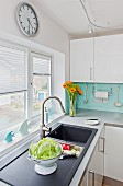 Modern, white kitchen corner counter; colander of lettuce on draining board below window with half-closed blinds