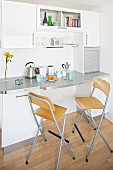 Bar stools with back rests at breakfast bar in kitchenette