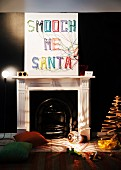 Christmas decorations in interior with fireplace; hand-crafted picture on wall with letters made from colourful woollen yarn, original floor lamp and wooden Christmas tree