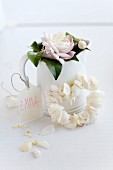 Wreath of threaded camellia petals against jug decorated with name tag and flower