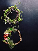 Wreaths of twigs and flowers on dark surface