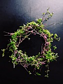 Hand-crafted wreath of twigs with leaves and purple flowers