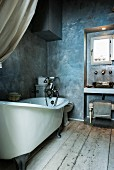 Narrow vintage bathroom with free-standing bathtub, rustic wooden floor and grey-blue marbled paint effect on walls