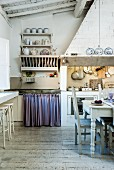 Rustic vintage kitchen with dining area in front of cooker below masonry extractor hood