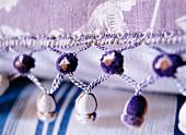 Kunstvolle Bordüre mit kleinen Bommeln an handgenähtem Kissen aus klassisch gemustertem Leinenstoff