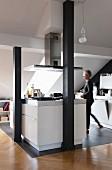 Kochbereich in ausgebautem Dachraum, Frau vor weisser Kochinsel auf grauem Fliesenboden, hinter schwarz lackierten Holzstützen