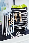 Black and white striped gift bags with wooden beads threaded onto handles on black table mat