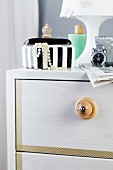 Furniture knob hand-crafted from wooden bead on chest of drawers