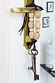 Key lanyard decorated with wooden beads hanging on brass door handle