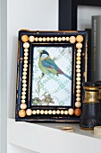 Picture of bird in frame decorated with wooden beads