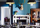 Dining room in eclectic mixture of styles with festively set table, antique glass-fronted cabinet & hunting trophy above open fireplace