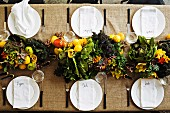 Set table decorated with centrepiece of fruit, vegetables & flowers