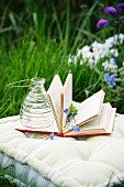 Wasp trap and flowers on open book on cushion amongst grass