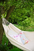 Floral cushion in ecru hammock hanging from tree