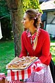Frau mit frisch gebackenem Apfelkuchen im spätsommerlichen idyllischen Garten