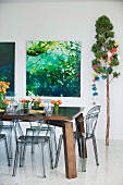 Mit Blumenschmuck gedeckter Massivholztisch und Kunstoffstühle in Rauchglasoptik; Naturfotografien und Baumstamm mit Origami-Girlande als Weihnachtsschmuck