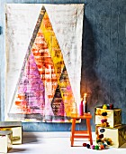 Artistic wall hanging of stylised Christmas tree on grey wall above presents wrapped in gold paper and lit candles