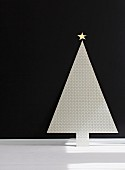 Minimalist, stylised Christmas tree cut from perforated sheet metal with gold star on top against black wall