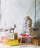 White construction paper Christmas tree held together by dowel with gold star on top on small 50s table next to wrapped present and stag figurine
