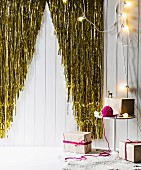 Silhouette of Christmas tree cut out of shiny lametta curtain on white board wall next to presents on table and fairy lights