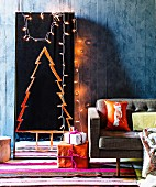 Stylised Christmas tree painted in orange paint on full-length mirror and fairy lights against blue-grey wall, colourful stripes rug and wrapped presents next to retro sofa